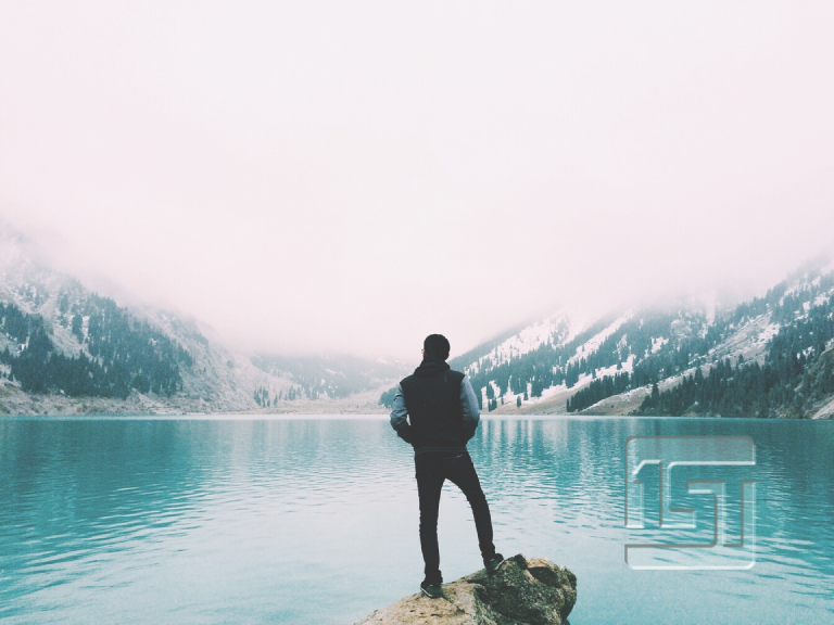 man looking out over the lake with foggy mountains in the background